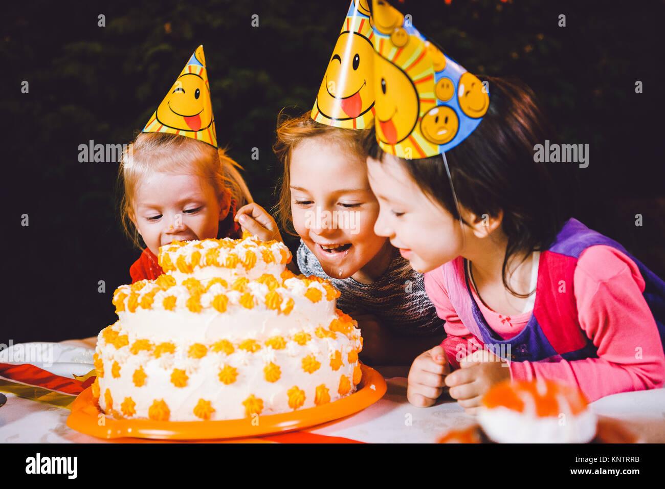 Festa di compleanno di bambini. Tre Allegri Ragazzi Ragazze a tavola a mangiare la torta con le loro mani e macchie Immagini Stock