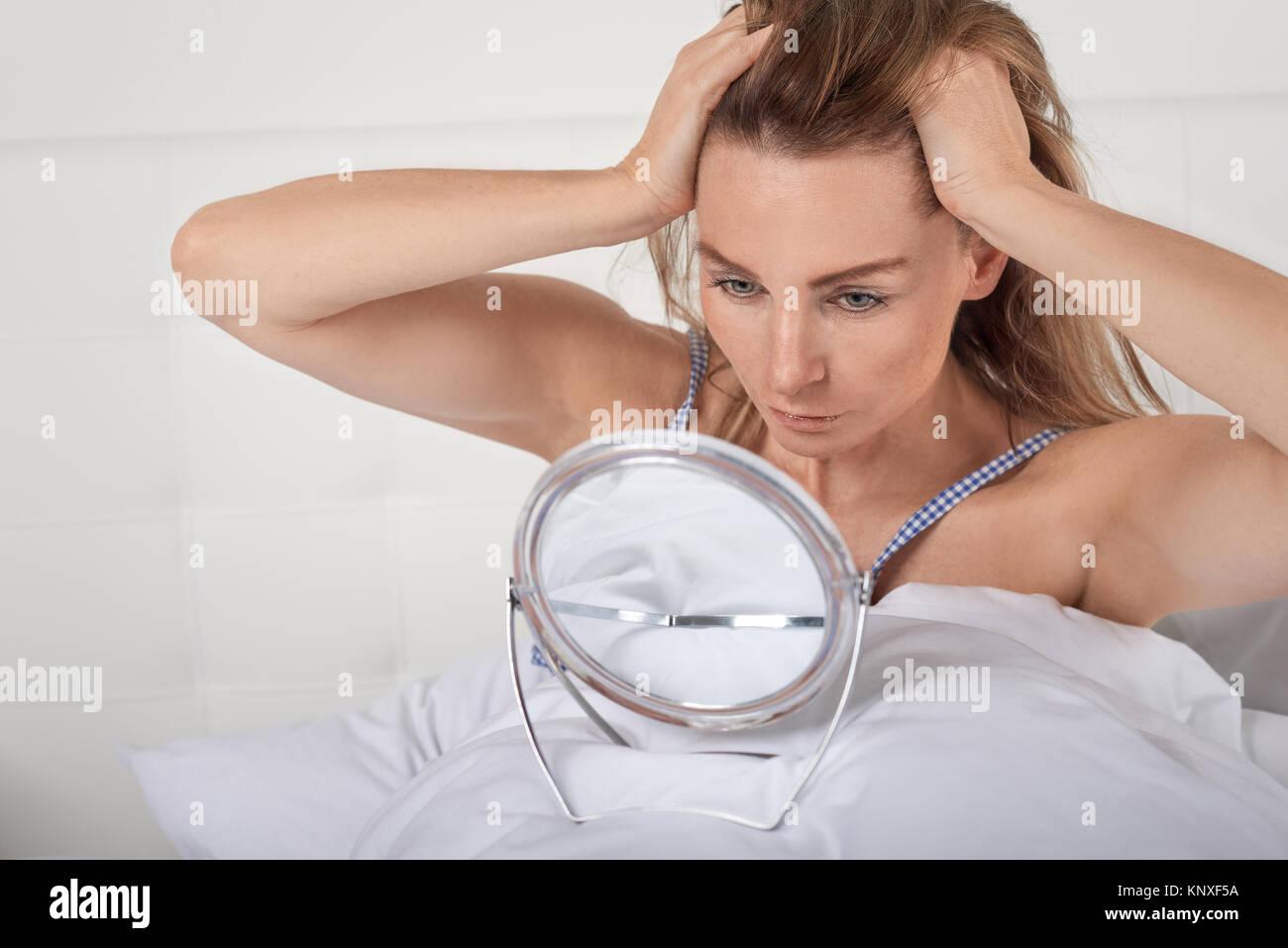 Grave giovane donna nel letto guardando a se stessa in un piccolo portatile a mano bilanciato a specchio sul coperchio Immagini Stock