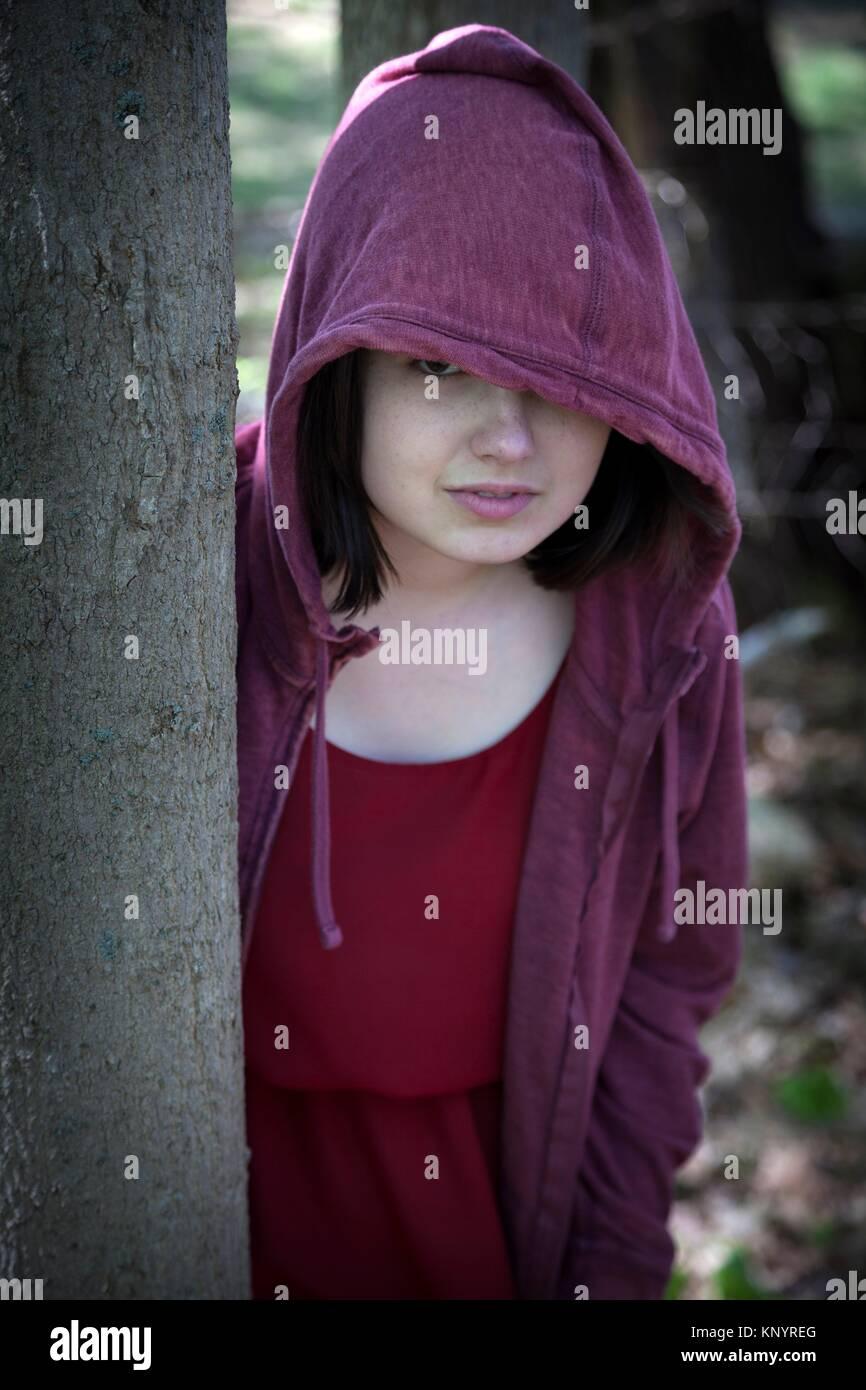 Giovane donna, appoggiata contro un albero in un parco, indossare una felpa rossa e la felpa con cappuccio. Immagini Stock