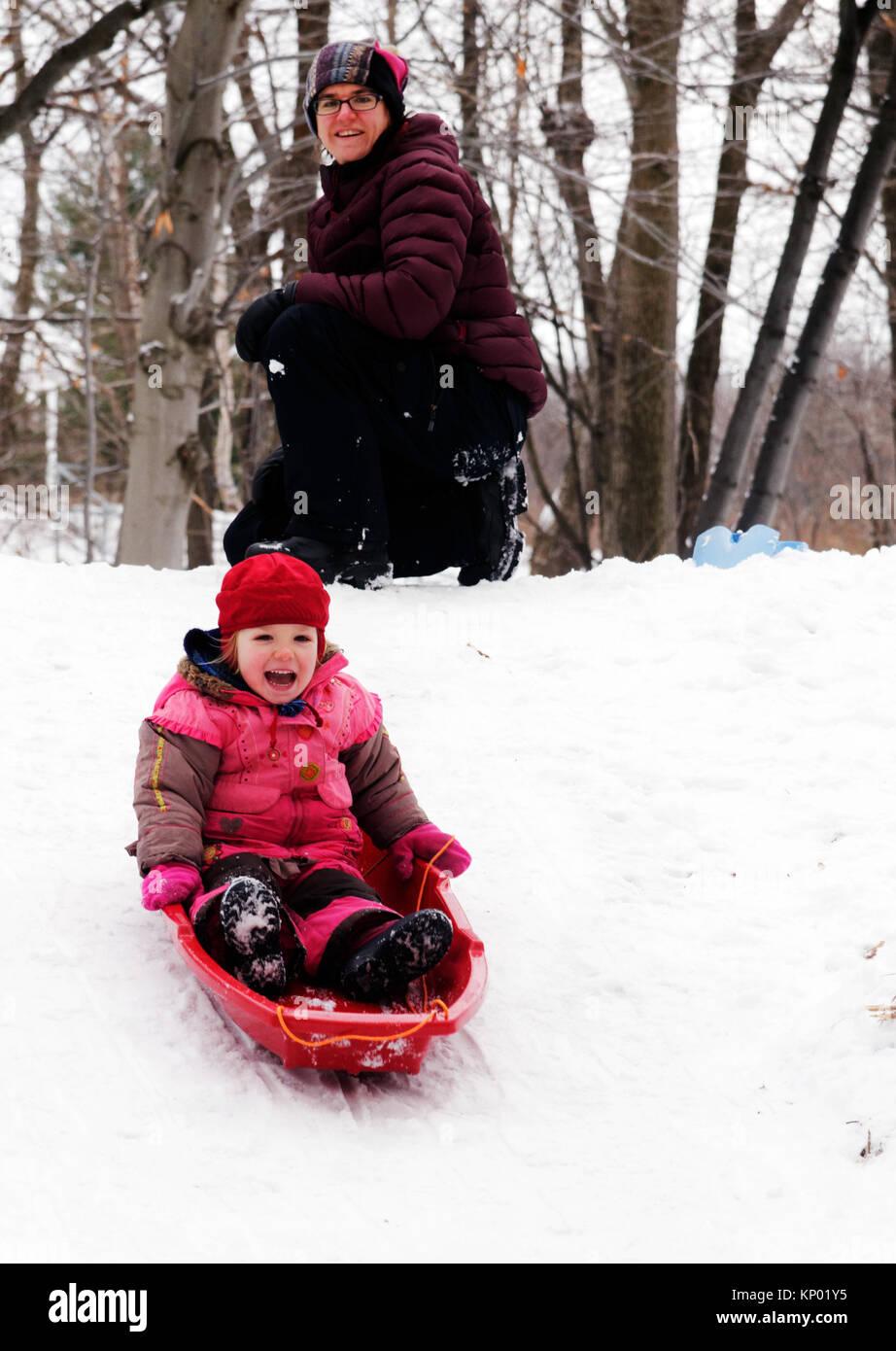 Una bambina (3 anni) in slittino Quebec, mentre la mamma si affaccia su Immagini Stock