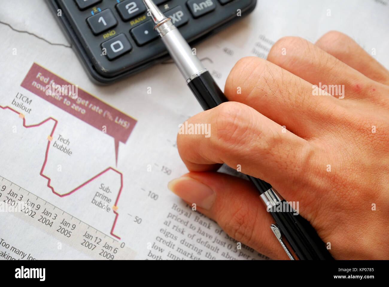 Primo piano della mano che scrive e documenti finanziari con la caduta di grafico del mercato azionario in background, Immagini Stock