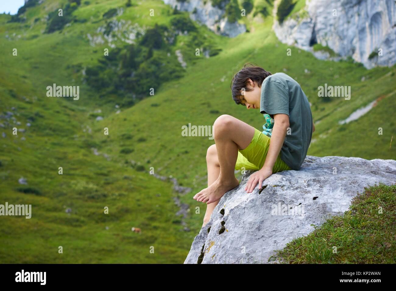 Oung pensieroso ragazzo seduto sulla roccia in montagna bavarese Brauneck, Germania Immagini Stock