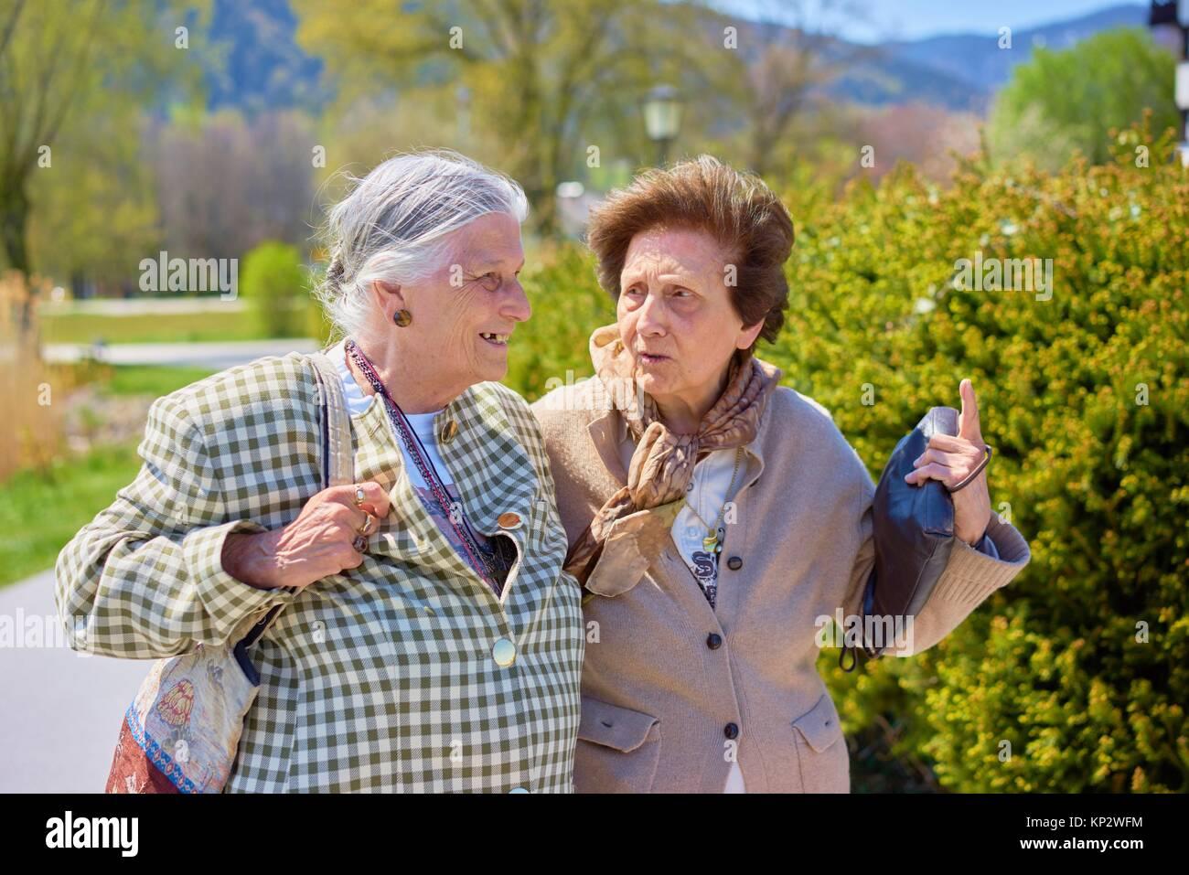 Felice Vecchio senior donne raccontare storie tra di loro in posizione di parcheggio Immagini Stock