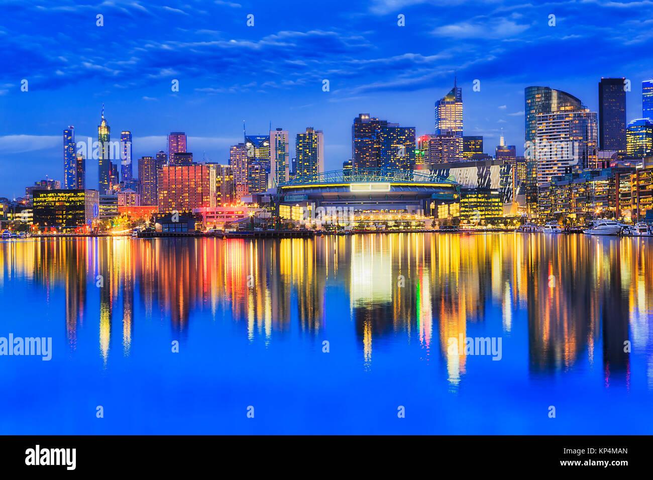 Luminose iilluminated waterfront architettura urbana di Docklands sobborghi di Melbourne riflettendo ancora in acque Immagini Stock