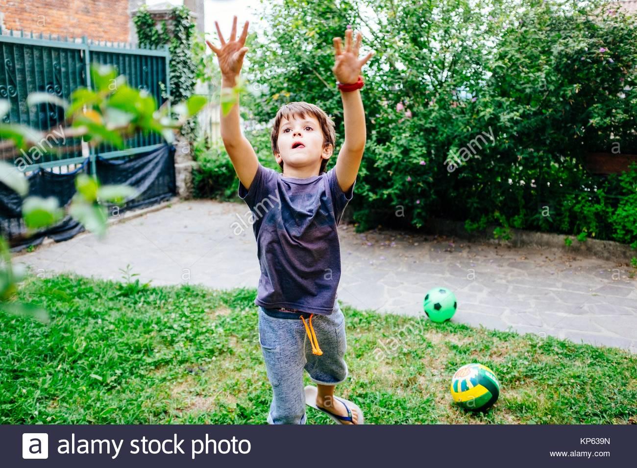 Bambino gioca palla nel giardino della casa Immagini Stock