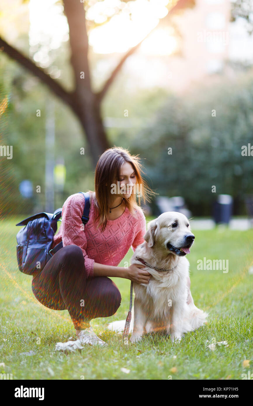 Foto di bruna con zaino sulla passeggiata con retriever Immagini Stock