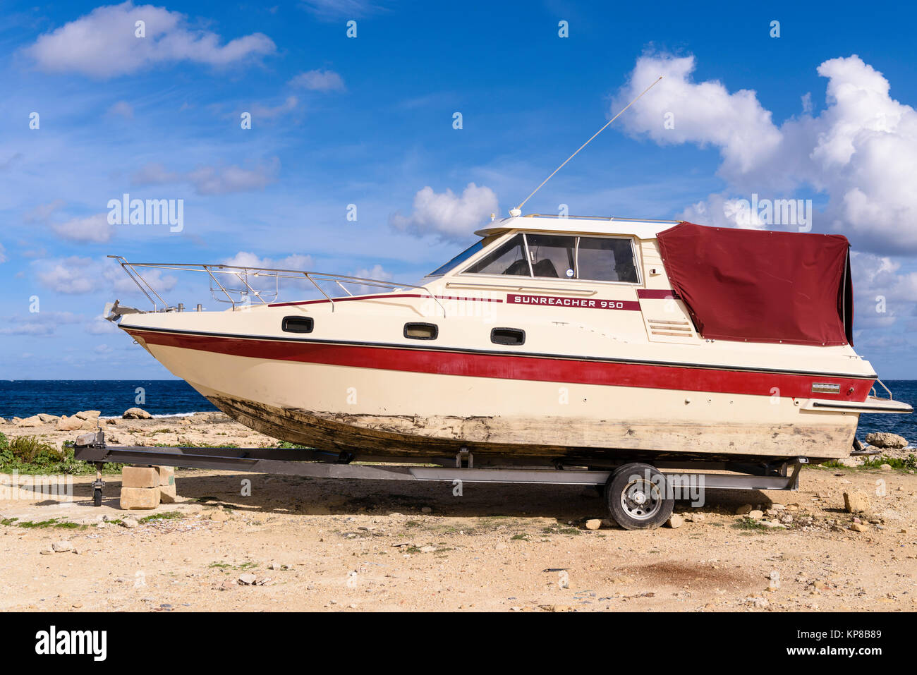 Vecchio Sunreacher 950 cabinato su un rimorchio parcheggiato a una costa rocciosa. Immagini Stock