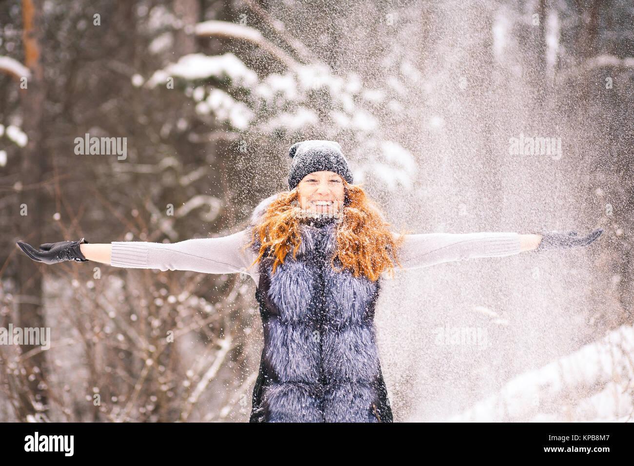 f538b24d68b8 Divertimento invernale. La ragazza di abbigliamento invernale gettando la  neve fino all'aria. Giovane donna gode nevoso inverno. Ritratto di donna  bella con ...