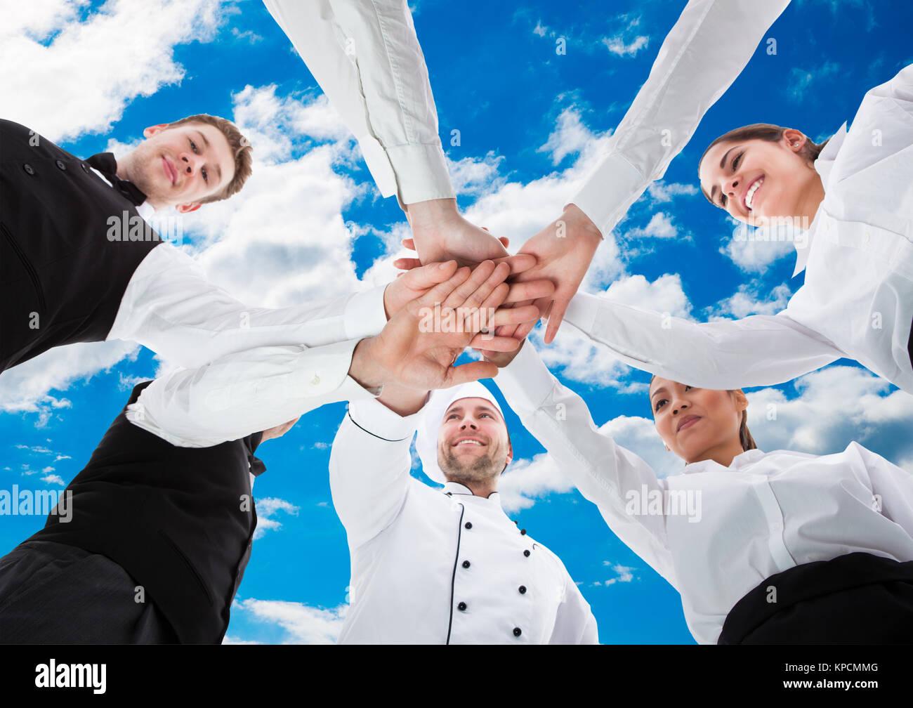 I camerieri e le cameriere mani di impilamento Immagini Stock