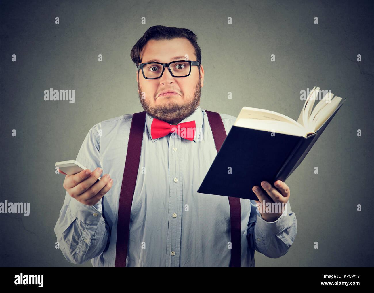 Chubby guy in bicchieri scegliendo tra il libro e la lettura dello smartphone. Immagini Stock
