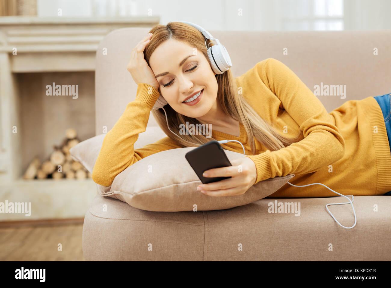 Donna sorridente rilassante sul divano e ascolto di musica Foto Stock