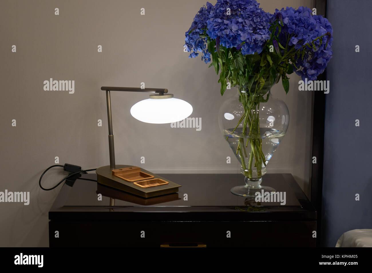 Lampada, comodino e un mazzetto di ortensie blu fiori in camera da ...
