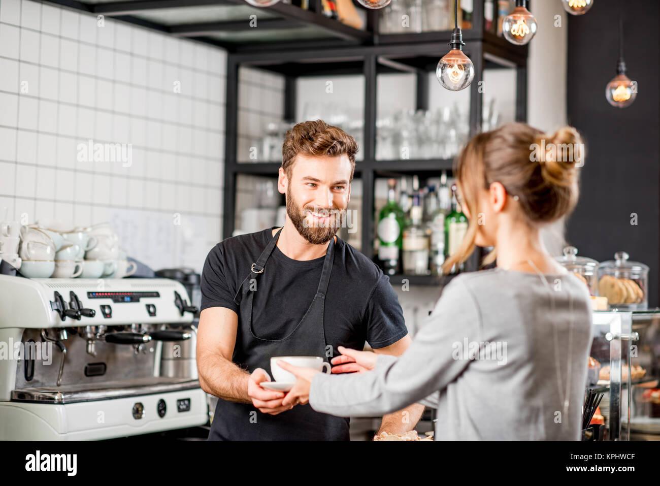 Barista con il cliente presso il cafe Immagini Stock