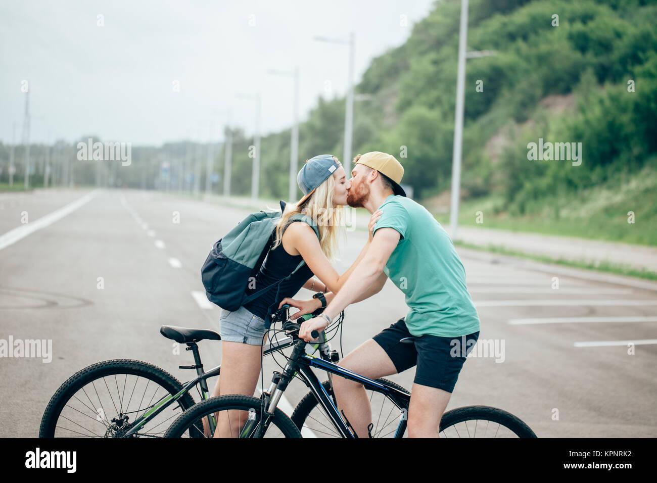 Romantico sport giovane kissing contro sfondo sfocato con biciclette Immagini Stock