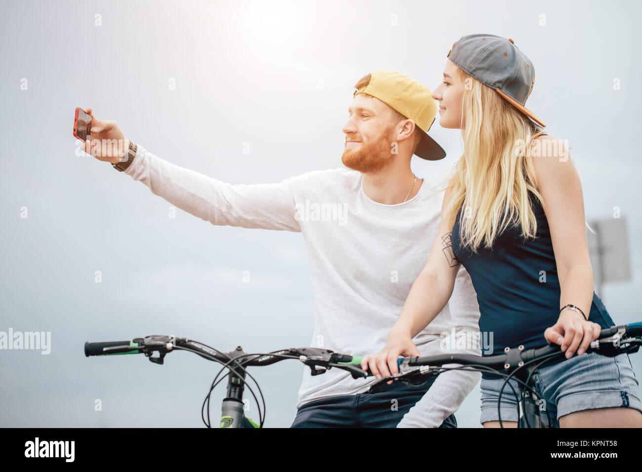 Coppia felice con la bicicletta prendendo selfie all'aperto Immagini Stock