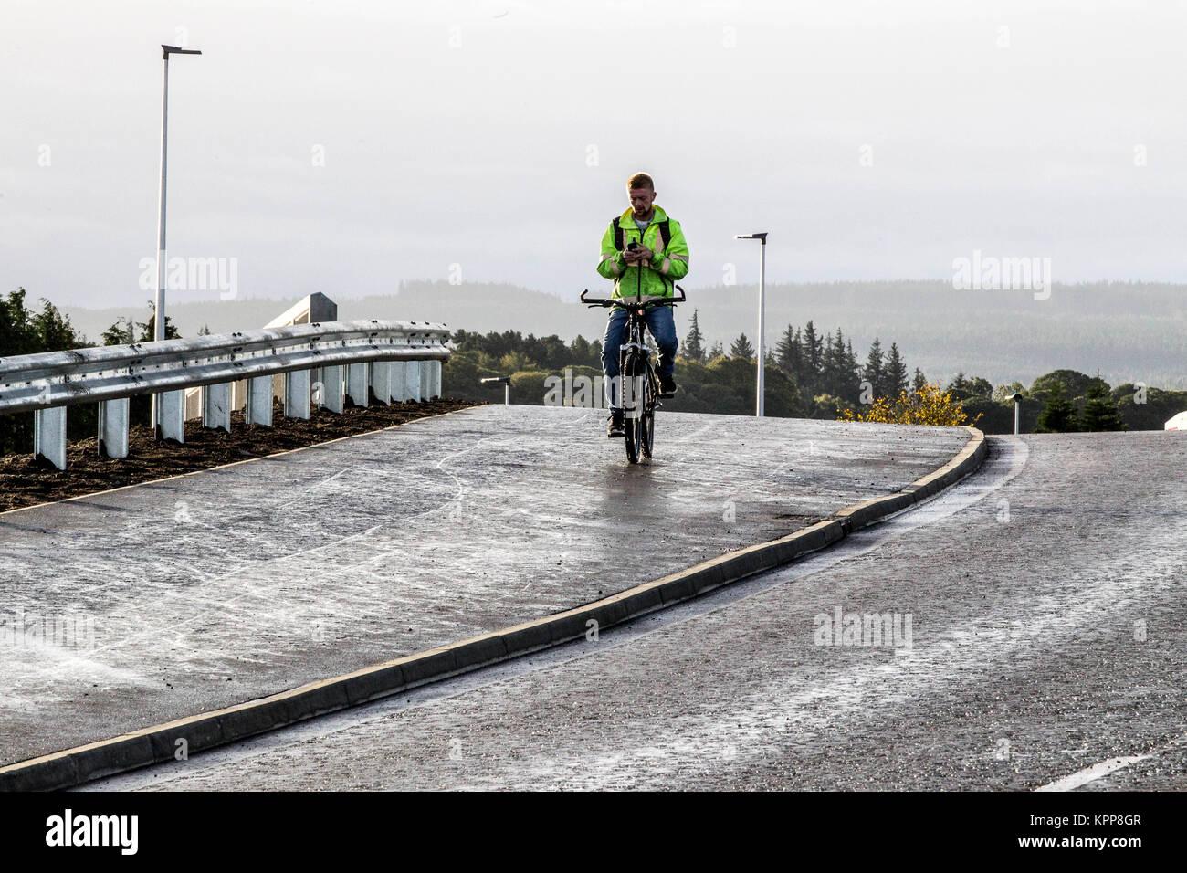Ciclista tramite telefono cellulare mentre in bicicletta sul marciapiede marciapiede/ Immagini Stock
