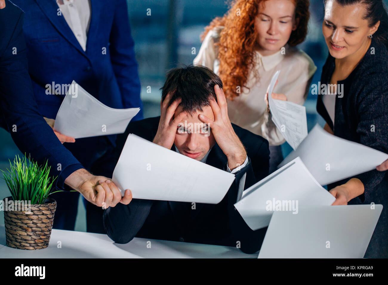 Ha sottolineato il business man in Office circondato da colleghi con documenti in mani Immagini Stock