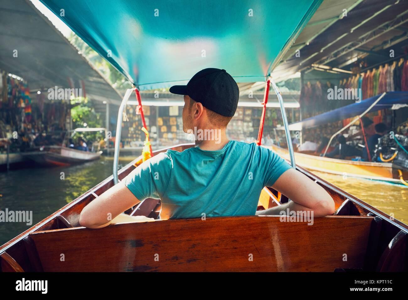 Giovane uomo (traveler) sulla barca. Tradizionale mercato galleggiante di Damnoen Saduak a Ratchaburi vicino a Bangkok, Immagini Stock