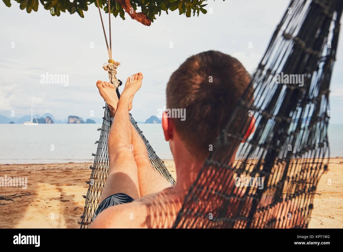 Giovane uomo (turistico) rilassante nella amaca sulla spiaggia di sabbia - il fuoco selettivo sul piede. Isola Koh Immagini Stock