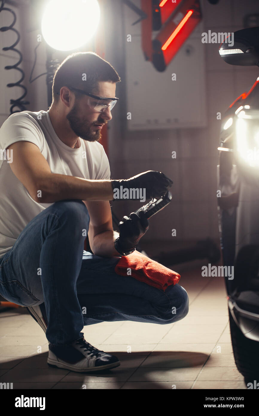 L'uomo controlla la lucidatura con una torcia Immagini Stock