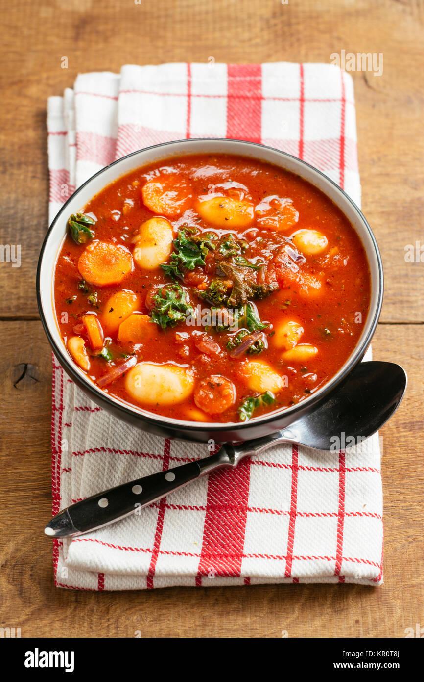 Gigantesca zuppa di fagioli con cavolo riccio, carote e patate. Immagini Stock