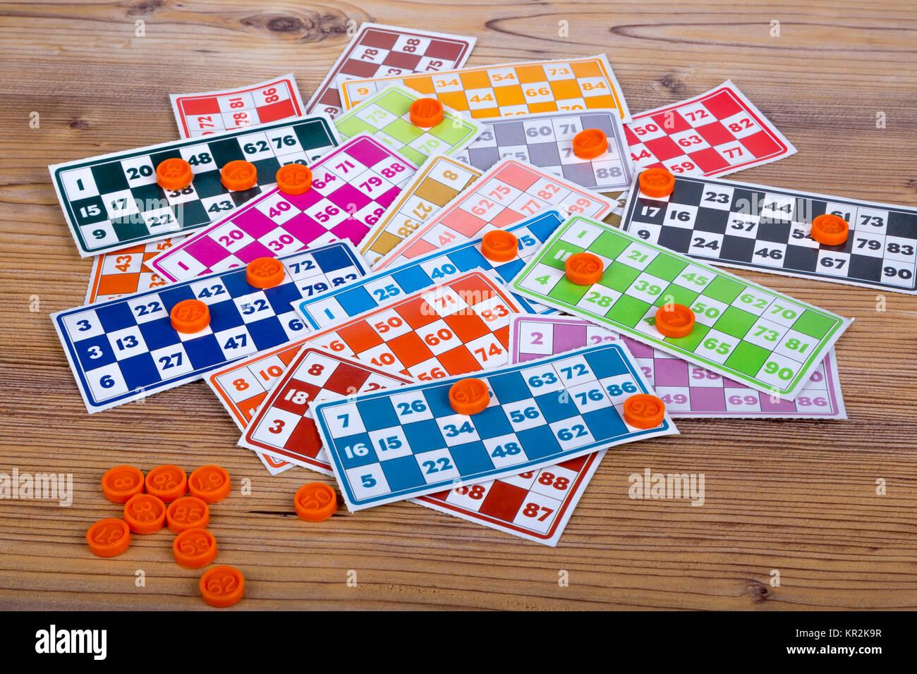 Colorate o lotto bingo gioco carte con i numeri e la plastica lotto di barili, su sfondo di legno. Immagini Stock