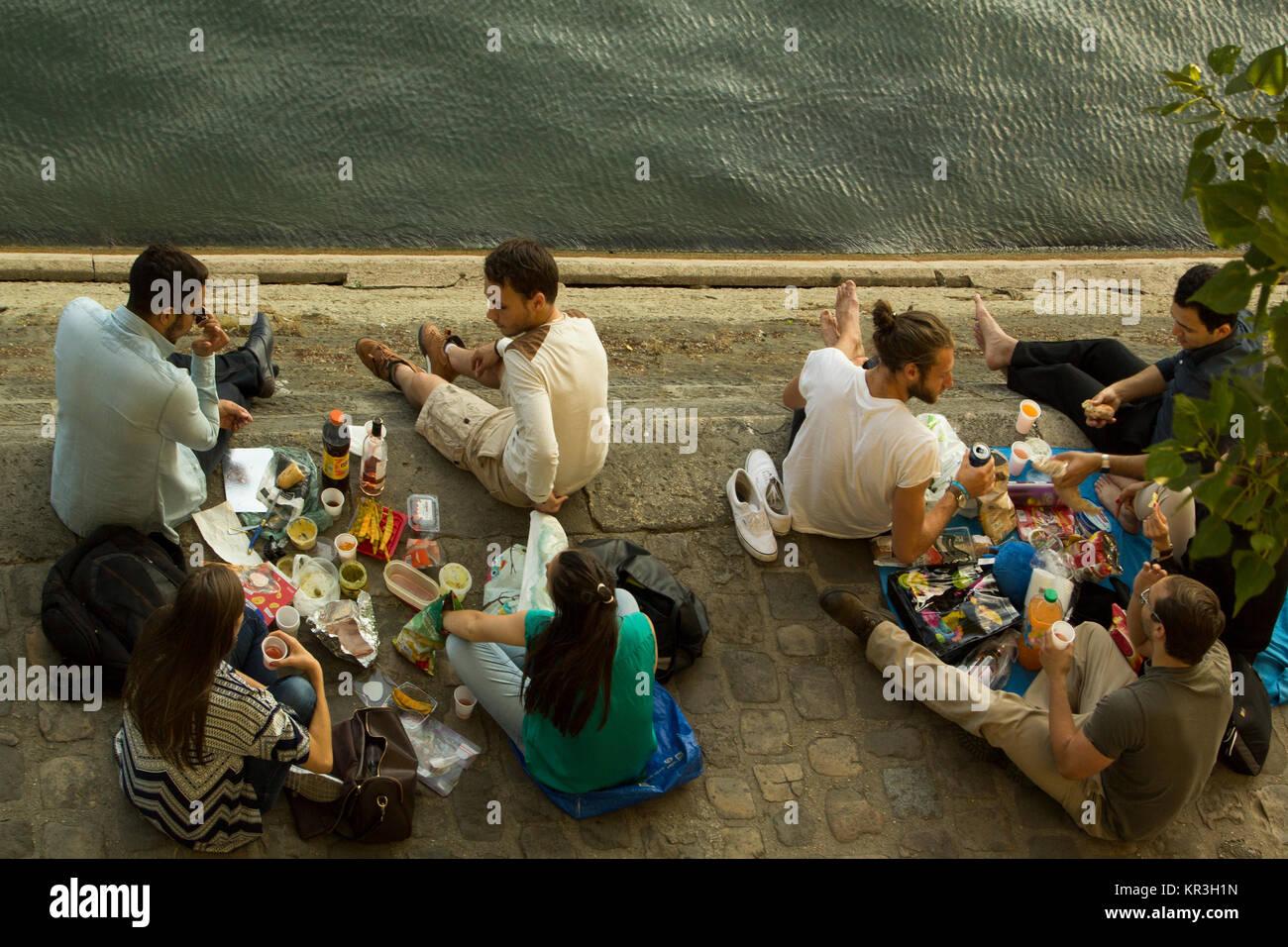 Molti giovani in un momento di relax a pomeriggio estivo in île Saint-Louis sulle rive del fiume Senna a Parigi, Immagini Stock