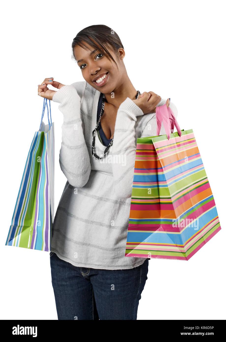 Un felice shopping ragazza sacchetti di contenimento e sorridente selvaggiamente circa il suo rabbioso il consumismo. Foto Stock