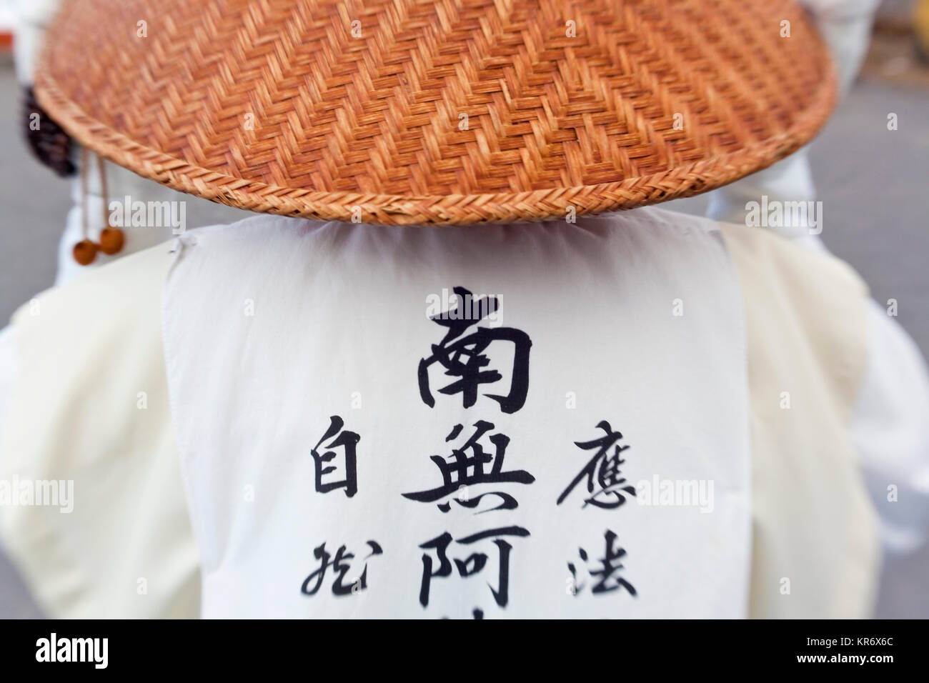 Vista posteriore della monaca buddista che indossa abiti tradizionali e cappello  di paglia. Immagini Stock 287f5e98ca25