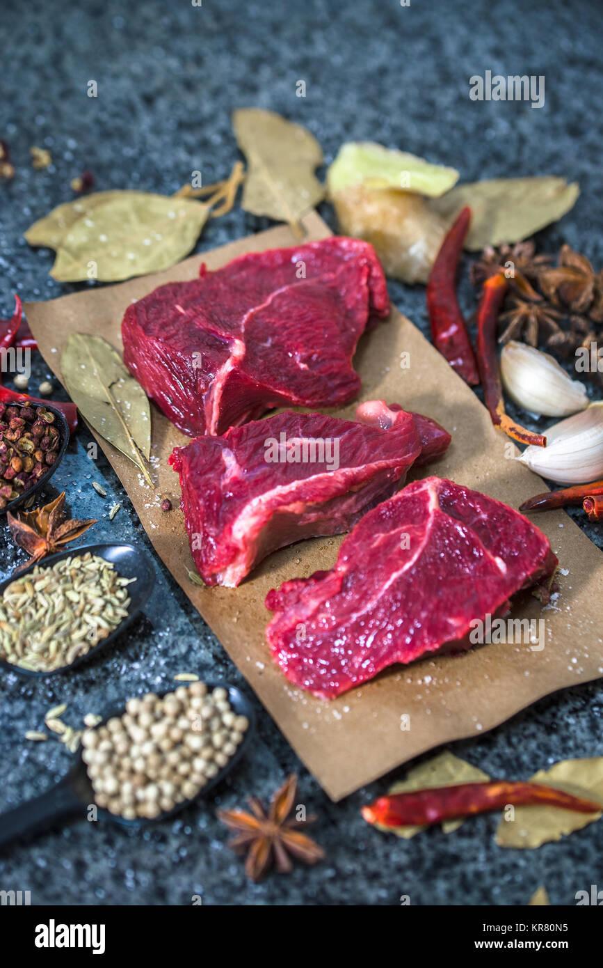 La carne cruda. Materie bistecca su un tagliere con rosmarino e spezie. Immagini Stock