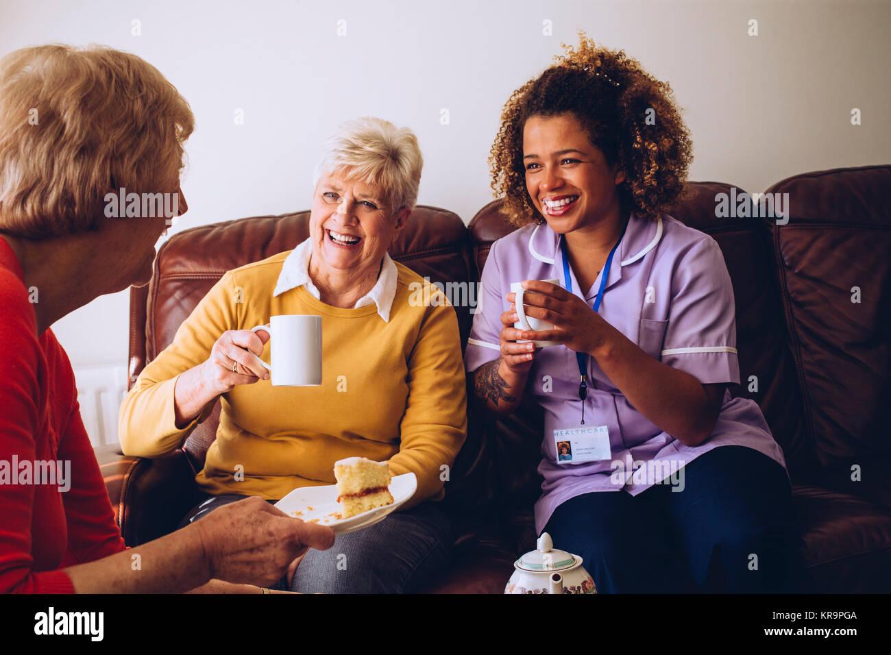 Operatore sanitario a condivisione di tempo di tè con i suoi pazienti Immagini Stock