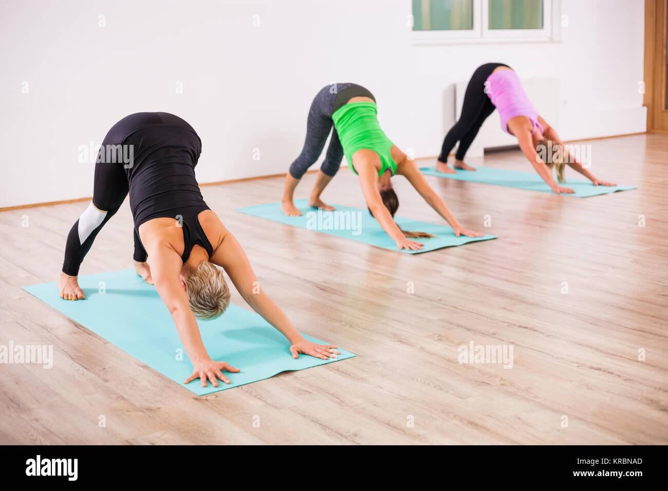 Le tre ragazze la pratica dello yoga, Svanasana / cane verso il basso rappresentano Immagini Stock