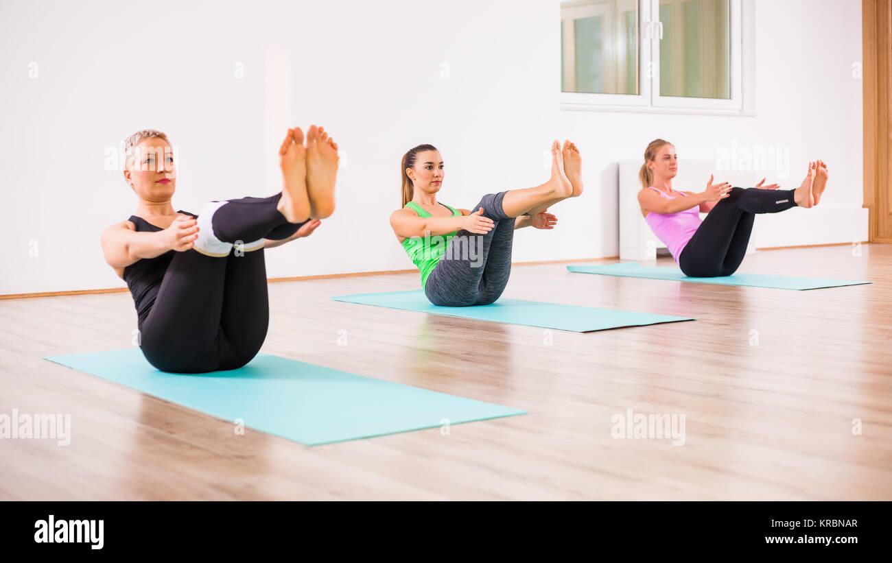 Le tre ragazze la pratica dello yoga, Navasana / Barca pongono Immagini Stock