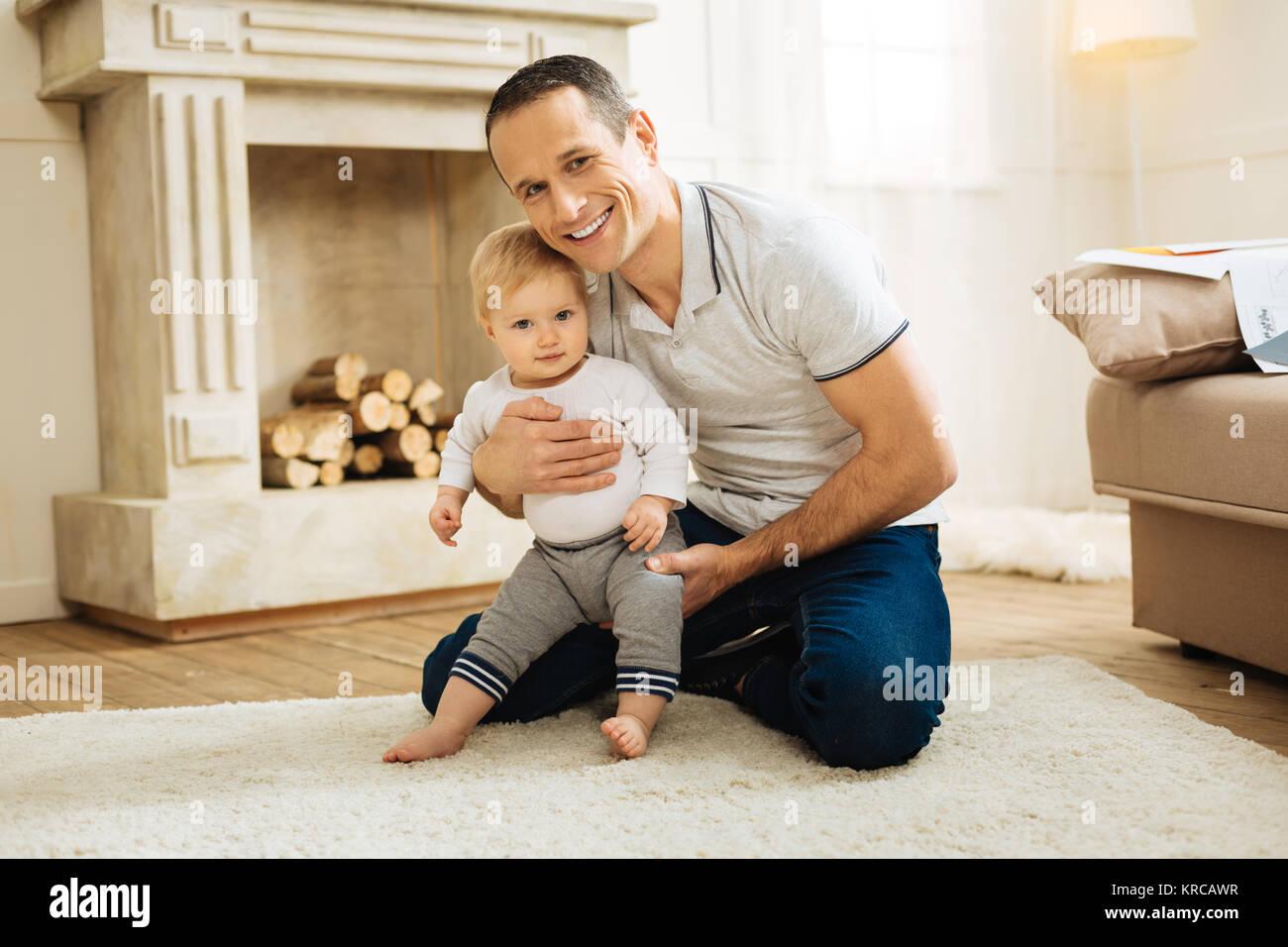 Felice giovane padre abbraccia il suo bambino mentre è seduto in una stanza vivente Immagini Stock
