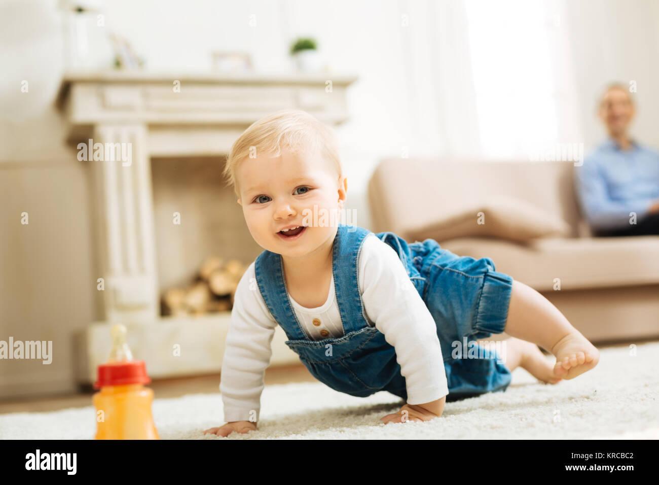 Positivo bambino bello cercando felice durante la riproduzione sul tappeto Immagini Stock