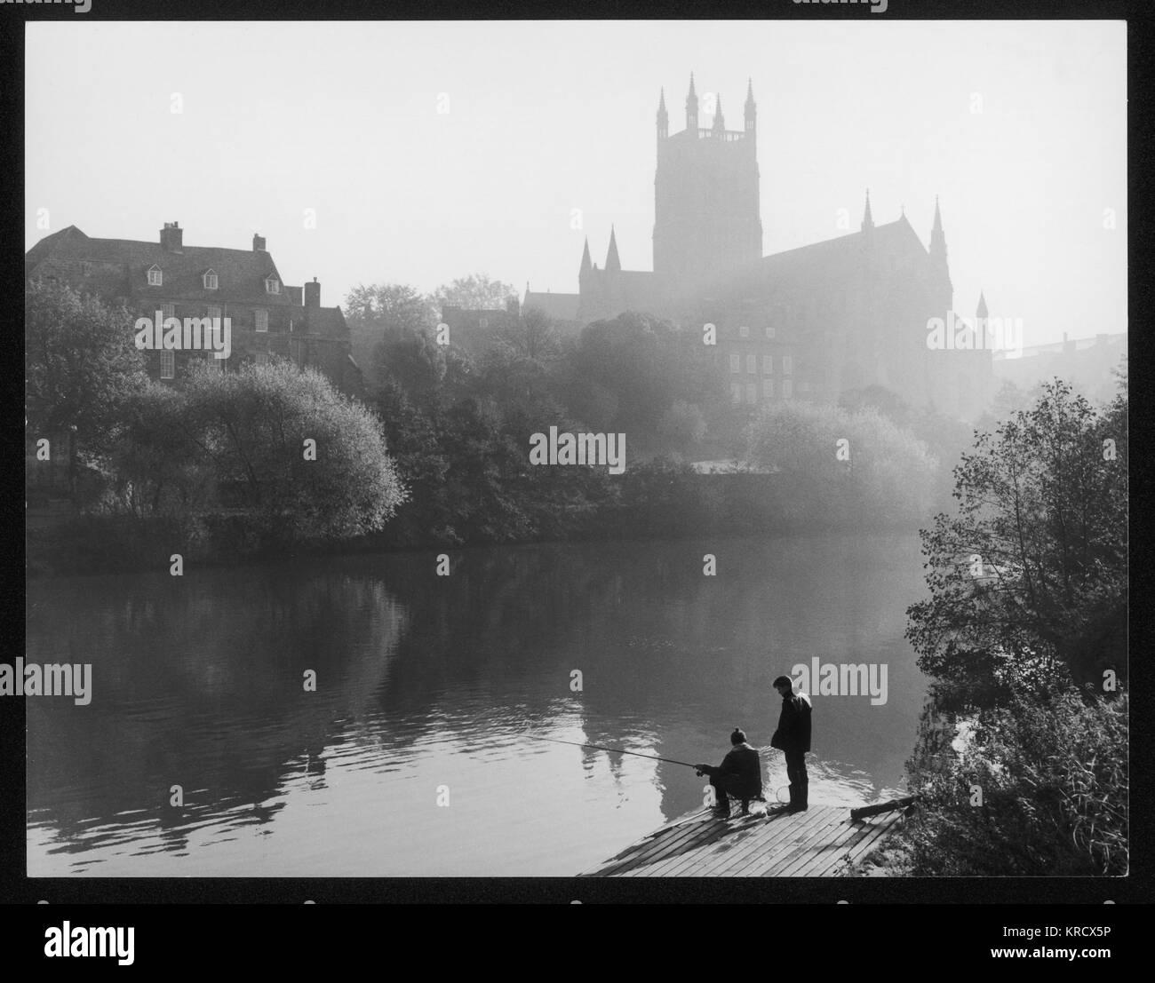 Pescare nel fiume Severn in una nebbiosa mattina, mentre il sole sorge dietro la cattedrale di Worcester in distanza. Immagini Stock