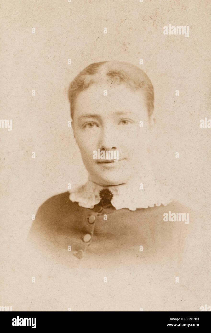 Una giovane donna in un testa e spalle fotografia, indossando un abito abbottonato con un collare bianco. Data: Immagini Stock