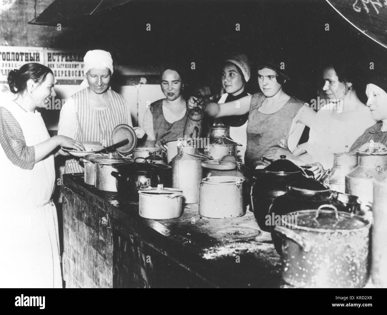 Sette donne trafficato stessi attorno ad un lavoro in pietra top adornata con una schiera di grandi teglie e pentole Immagini Stock