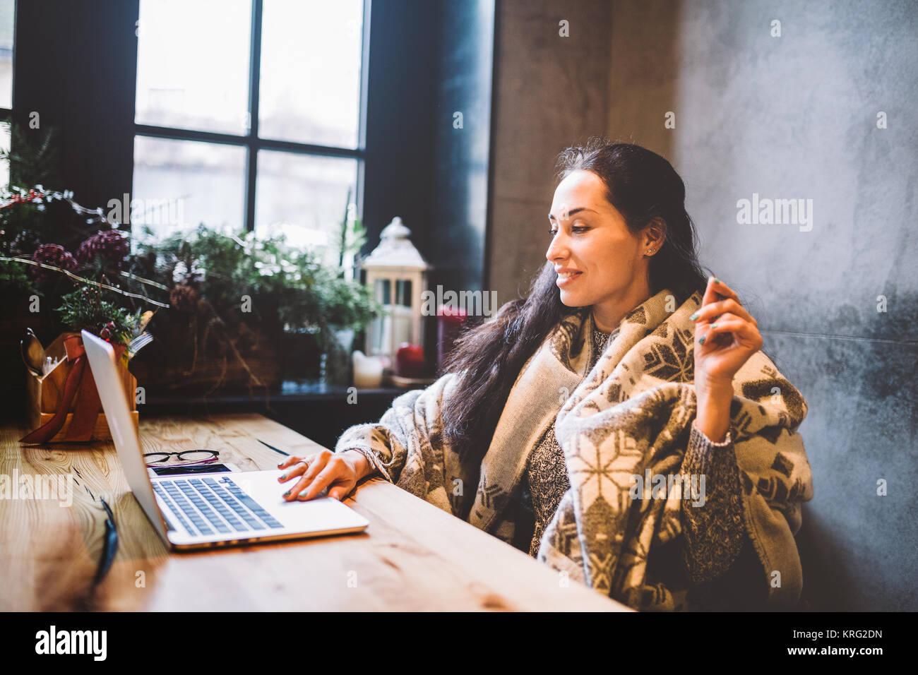 Bella ragazza giovane utilizza la tecnologia portatile, testo tipi guardando il monitor in un caffè dalla finestra Immagini Stock
