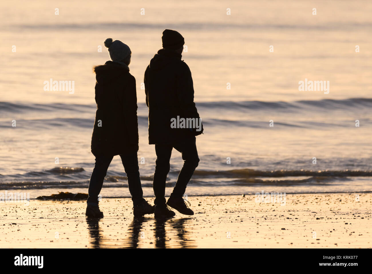 Silhouette di un paio di fare una passeggiata in riva al mare nella luce della sera. Immagini Stock