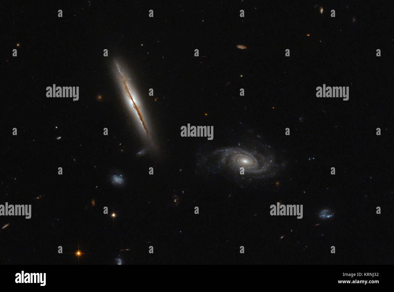 Nonostante il suo aspetto modesto, il bordo-sulla galassia a spirale catturati nella metà di sinistra di questo Immagini Stock
