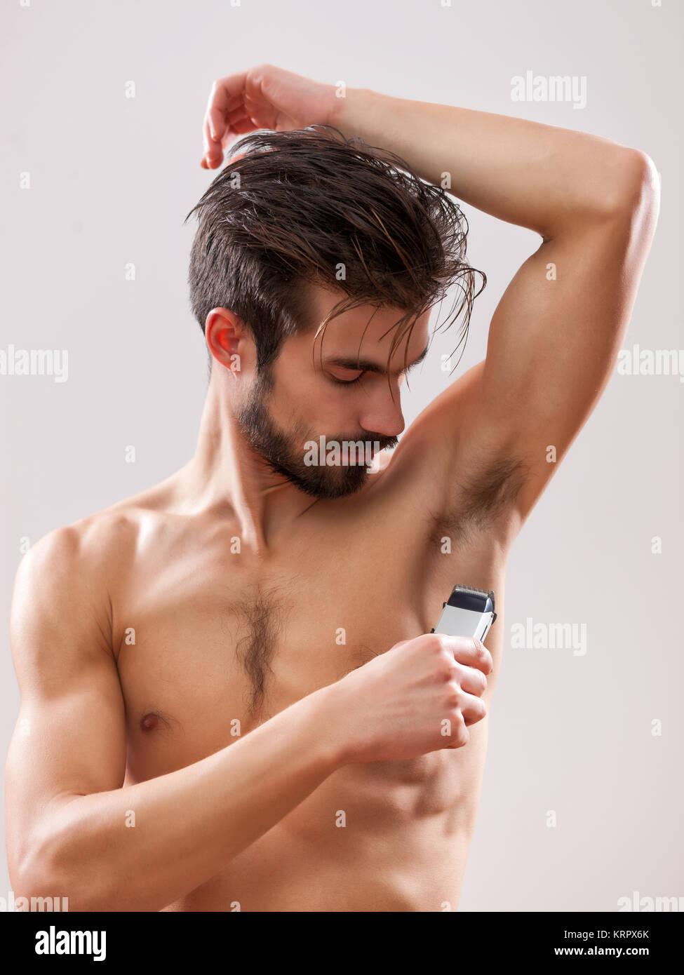 Giovane uomo bello è la rasatura la sua ascella con rasoio elettrico. Immagini Stock
