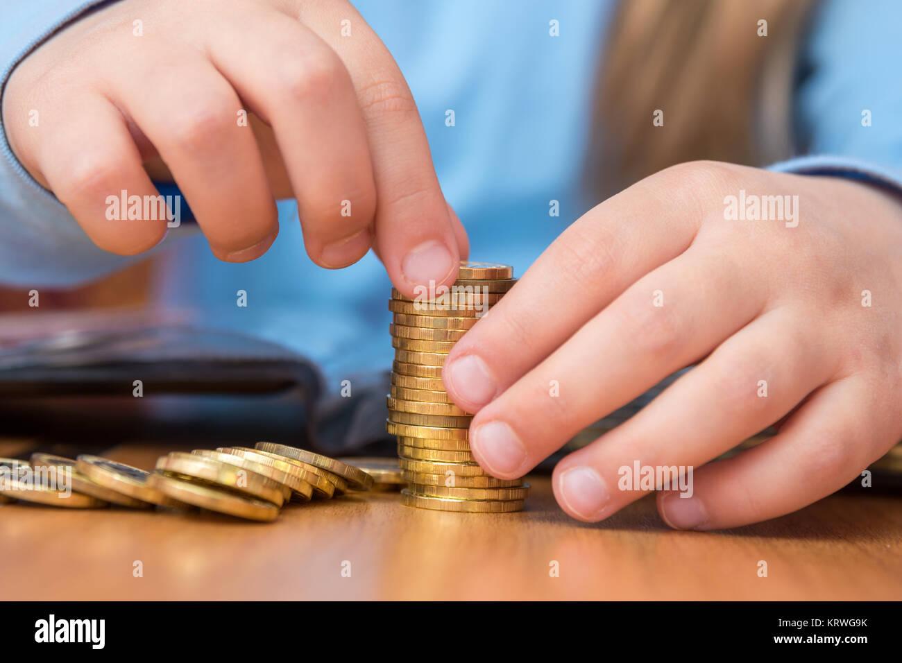 Bambino raccoglie una pila di monete d'oro, close-up Immagini Stock