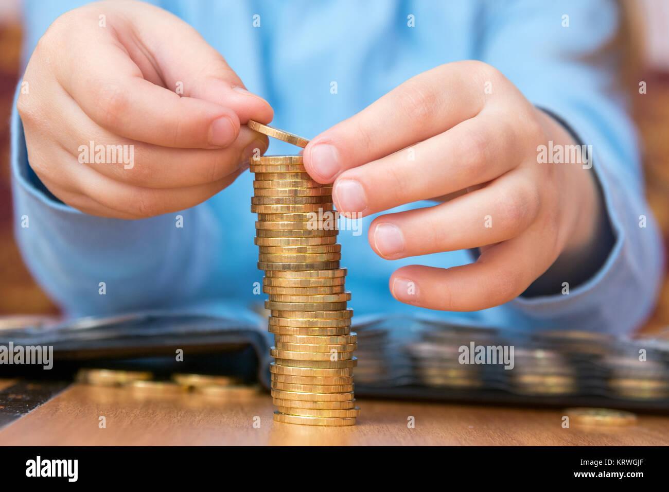 Bambino accumulato un gran mucchio di monete d'oro, close-up Immagini Stock