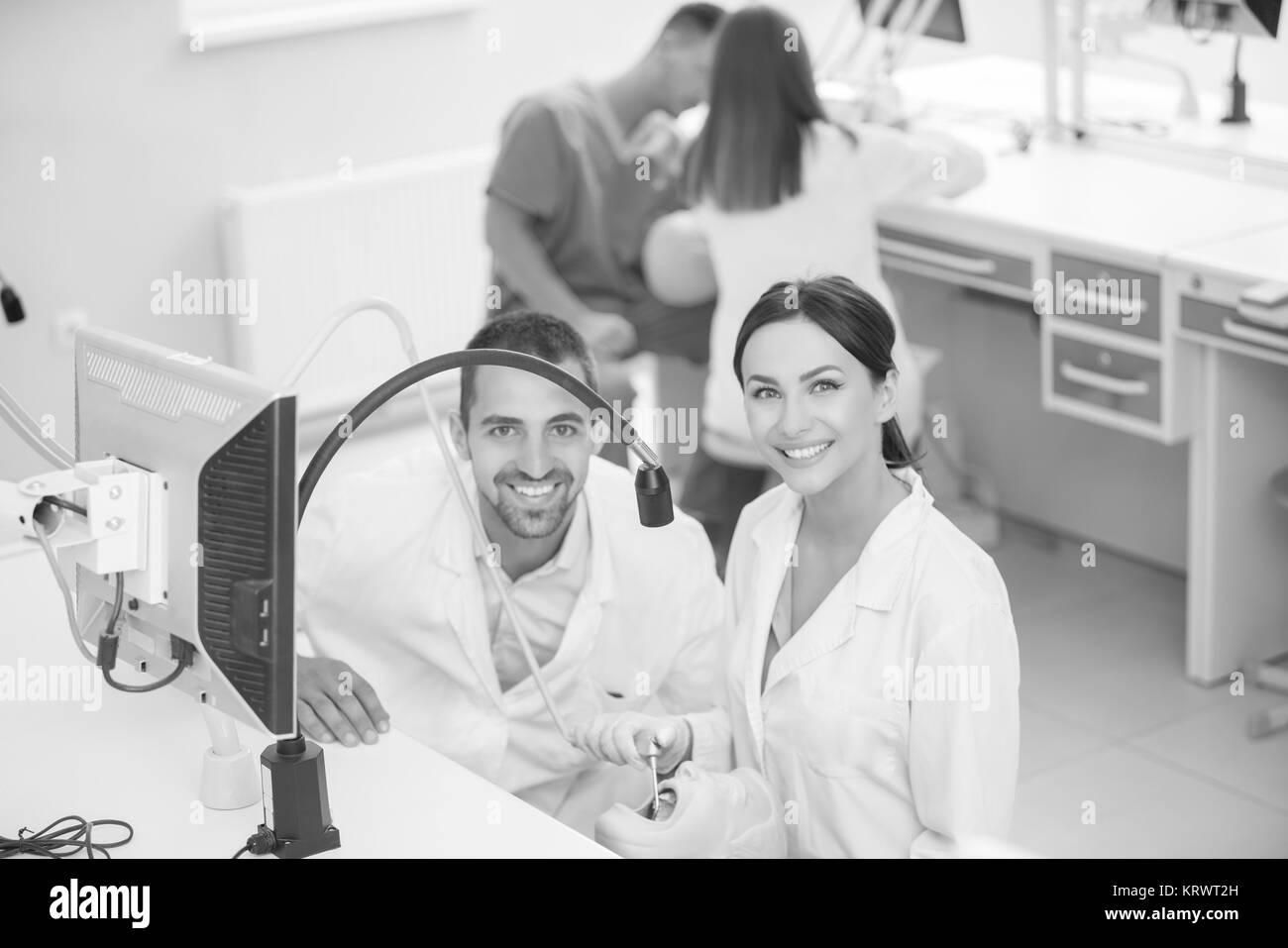 Dentiere, igiene orale. Protesi le mani mentre si lavora sulla dentiera, falsi denti, uno studio e una tabella con gli strumenti odontoiatrici. Foto Stock