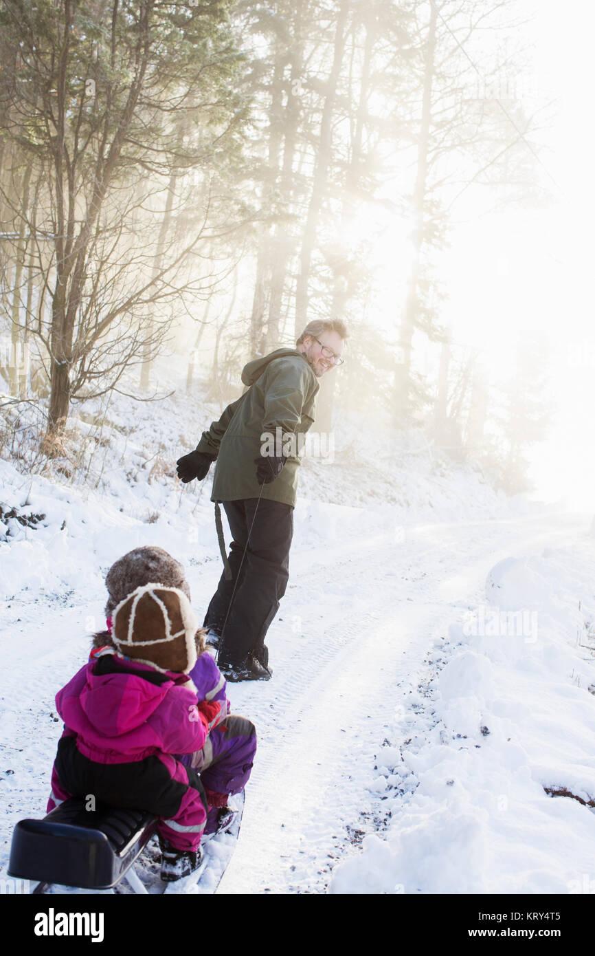 Un padre tirando le sue due giovani figlie su una slitta Immagini Stock