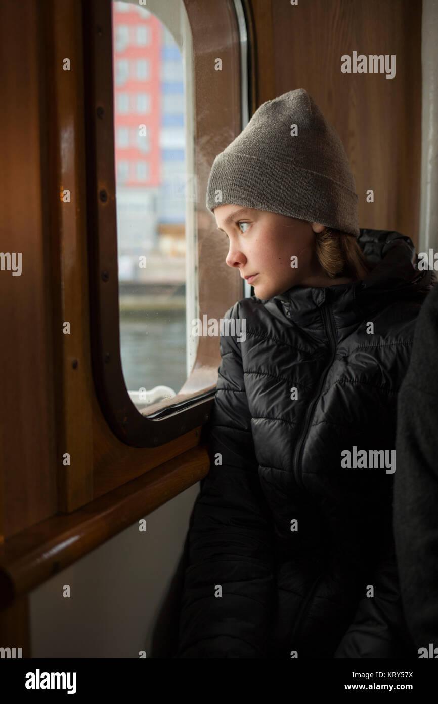 Ragazzo che guarda fuori da una finestra in barca Foto Stock