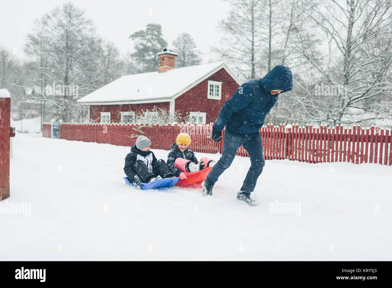 L'uomo tirando i bambini sulla slitta Immagini Stock