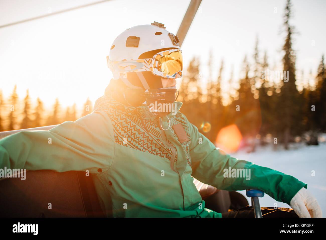 Uomo che indossa gli occhiali e casco al tramonto in Osterdalen, Norvegia Immagini Stock