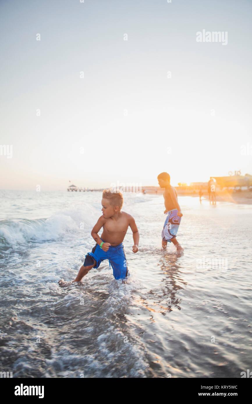 I bambini che giocano nel surf su una spiaggia in Turchia Immagini Stock